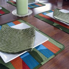 "This contemporary, placemat/napkin set of four will top your table in bold style. Three colors of Marimekko ""Kivet"" are stitched and quilted to form beautiful color blocks of pattern in green, blue and orange. Kivet is Finnish for ""stones"" and you will love the movement of the print with large, irregular curved lines. Marimekko ""Sade"" is used for the placemat backing and the cloth napkins."