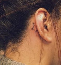 Behind-the-ear floral tattoo by Nando