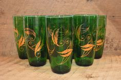 Vintage Green Glass with Gold Leaf Tumblers Set of 7  Measures: 5 3/4 inches tall with a 3 inch diameter  Good Vintage Condition with no chips or breaks. There is some wear to the gold leaf design, which can be seen in the photos. We are happy to combine shipping if you are interested in more than one item. Shipping is calculated by ETSY according to your specific zip code, but we also refund shipping overages beyond $2.00 For more great vintage finds including lots of great glassware visit…
