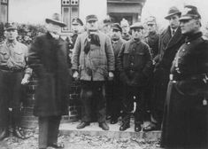 Jews arrested during Kristallnacht stand under guard before being deported to the Sachsenhausen concentration camp. Zeven, Germany, November...