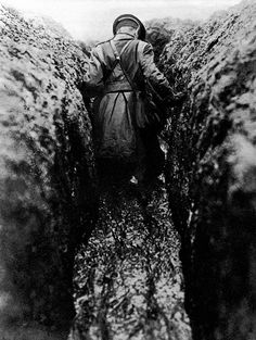 WW1, 1916. Winter on the Western Front. Officer wading through a trench of half frozen mud.