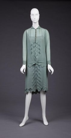 1926 Two piece jade green silk crepe dress, v-front, fabric button loops, round, silver buttons, three tier scallop motif at center front of over blouse, cuffs, center front of skirt and at skirt hem, machine smocking at shoulder.