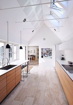 Lovely open and bright kitchen with high ceilings and kitchen elements in elm that brings a warm look to the large room.
