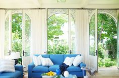 Airy and bright living space with bright blue sofa and white pillows