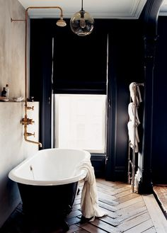 Black with white tub, wood floors and expose shower. Beauty.