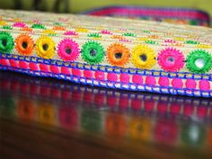 Multi-Color Embroidered Mirror Sequins Work Lace in yellow, orange, magenta, blue, green on beige cotton silk fabric for silk sari border. Trim is approx 1.3 inches wide. This stunning lace can be...