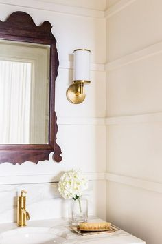 Alyssa Rosenheck - Jason Arnold Interiors - Black and gold powder room features paneled walls lined with a black metal industrial washstand topped with white marble framing a round sink paired with a modern gold faucet placed under a carved wood mirror lit by Studio VC Cylinder Sconces.