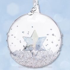 "The 2014 Christmas Ball Ornament is the second edition in a series of Ball ornaments. It hangs daintily on a white satin ribbon with a silver-tone metal tag showing the year of issue, 2014. Clear outer ball with sparking crystal star inside, the ball is 3.75"" High."
