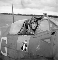 "W/C Ian R ""Widge"" Gleed sits in the cockpit of his Spitfire Mk Vb R-G at RAF Ibsley on 16 June 1942 while leading the Ibsley Wing. As a wing leader he was entitled to use personal markings instead of the usual squadron codes, and he used his initials on his personal mount. Gleed's personal emblem, depicting Figaro the cat swatting a swastika, is shown on the door panel beneath the cockpit. The cartoon cat first appeared in Walt Disney's animated film Pinocchio released in February 1940."
