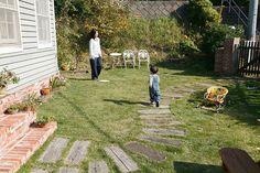 庭で遊ぶ修司くんと雅子さん。夫妻で芝を貼り、木を植えるなどガーデニングを楽しんでいる。