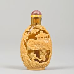 Glass Chinese snuff bottle of oval form, the yellow overlay on translucent amber ground carved with a continuous landscape of pavilions, rocks, lingzhi fungus and prunus, bamboo and pine tree (the three friends of the winter). 1780-1850 6,7 cm