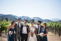 Wedding party standing in front of vineyard and mountains @myweddingdotcom
