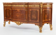 A FRENCH LOUIS XVI-STYLE MAHOGANY, SATINWOOD AND GILT BRONZE SIDEBOARD . Circa…
