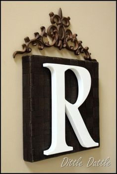 Cute and easy!  A block of wood, a wooden letter, and an iron scroll.  Great bridal shower gift.
