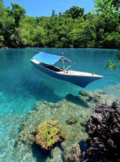 A boat in Sulamadaha beach, Ternate, Indonesia | Amazing crystal clear waters