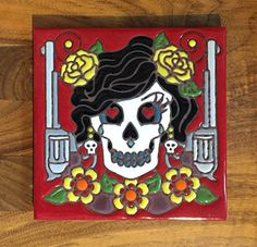 """6""""x6"""" Dia de los Muertos Bandita hand glazed tile trivet. This trivet is hand glazed on Italian quarry tile and fired at over 1,800 degrees making it completely weatherproof, fade-proof & great for kitchen use. Cork backed so it won't scratch your tables. This is a hand painted item, slight variations in color and small imperfections are to be expected and are caused by the human touch."""