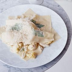 Cauliflower and Crab Ravioli | These impressive supersized ravioli are constructed with large rectangles of homemade pasta that are dotted with whole parsley leaves and filled with the unexpectedly alluring combination of crab and cauliflower.