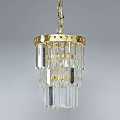 Shop Gala Chandelier.  You don't have to be royalty to hang a glass chandelier in your home.  With a gold metal frame featuring intricate triangle cut outs, this three-tiered pendant adds a touch of elegance anywhere you hang it.