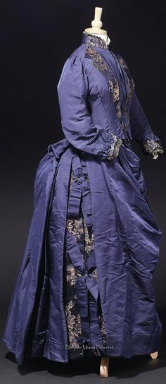 Afternoon dress, Maison Le Blond, Miss Wellington Successeur, London, ca. 1885. Midnight blue silk satin trimmed with blue brocade figured with golden metallic thistles, roseheads, & shamrocks. Bodice closes front with fabric-covered buttons concealed by pleated plackets leading to brocade faux lapels. Stand collar & cuffs trimmed with brocade, lace, & bows. Bustle skirt draped front & back with 2 inverted pleats of brocade, one with hanging bows. Bonhams