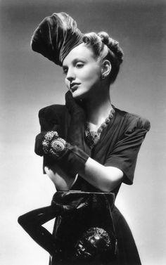 Model Meg Mundy wearing fashions by Schiaparelli - dress, jewelry, hat - in a 1940 photo by John Rawlings
