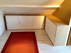 Série de placards sous pente pour l'optimisation d'un bureau. Ensemble en médium, portes laquées coulissantes, étagères réglables sur pistes perforées.
