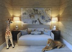 Safari themed boy's bedroom features planked walls lined with a safari postcard art piece placed over a gray nailhead daybed dressed in gray bedding, gray giraffe pillows, gray lion pillows and a gray Union Jack bolster pillow flanked by brown steamer trunk nightstands topped with glass column lamps filled with teddy bears alongside a plush giraffe and lion.