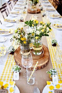 Jam jars of flowers on tree trunk slices. Hessian runner on top of fabric runner for table decoration.