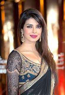 Priyanka Chopra posing at a film festival in dark sari looking towards the camera