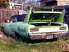 "An abandoned car that appears to read ""Plymouth""."