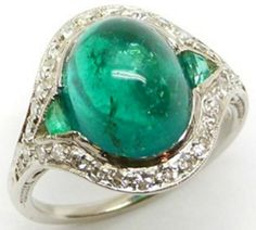 Art Deco emerald and diamond ring, circa 1930. The center stone is a large, oval cabochon-shaped emerald flanked by tapered baguette emeralds and with a diamond set border. Via Diamonds in the Library.