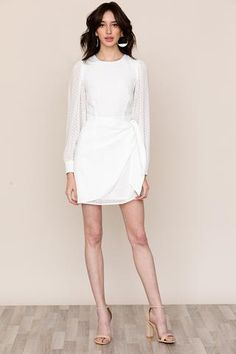 Our simple, yet classy Wonderland white long-sleeve mini dress checks all the boxes. Details include a faux wrap mini skirt, long blouson sleeves, and button cuffs. Lined with hidden back zipper. Simple Elegant Wedding Dress, Simple White Dress, Mini Dress With Sleeves, Long Sleeve Mini Dress, Classy Dress, Classy Outfits, Simple Short Dresses, Ankara Gown Styles, Rehearsal Dress
