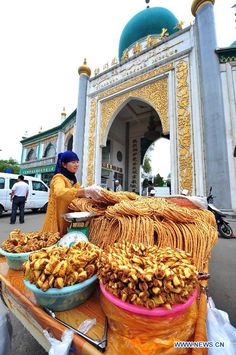A citizen buys Sanzi, a traditional snack of Moslems, ahead of Eid al-Fitr festival in Yinchuan, capital of Ningxia Hui Autonomous Region, Aug. 17, 2012. Eid al-Fitr festival, which falls on Aug. 19 this year, marks the end of the fasting month of Ramadan. (Xinhua/Peng Zhaozhi)