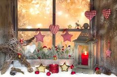 Christmas window decoration ideas with garlands, candles and displays.