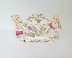 Beautiful vintage trinket box for the boudoir vanity or dresser. Features a young Victorian boy and girl on the front each holding grapes.