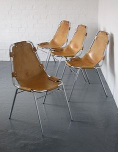 Les Arcs chairs designed by Charlotte Perriand in the 1960s for the Les Arcs ski resort. Chromed frames with light tan leather sling seats and metal fixings.