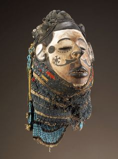 Africa | 'Maiden' mask from the Igbo people of Nigeria | Wood, textile, plant fiber, glass beads, metal, buttons, kaolin, encrustation