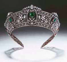 A MAGNIFICENT ANTIQUE EMERALD AND DIAMOND TIARA Comprising seven graduated step-cut emeralds set within sprays of diamond flowerheads and leaves, running between borders of continuous diamond collets and ribbon motifs, mounted in silver and gold, circa 1900, 43.8 cm. inner circumference.