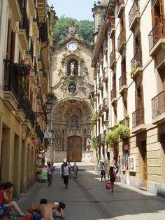 """La """"Parte Vieja"""", así llaman al casco antiguo de San Sebastián, callejuelas estrechas que van a morir a la ladera del Urgull. Una de ellas, al fondo, enmarca la fachada barroca de la basílica de Santa María"""