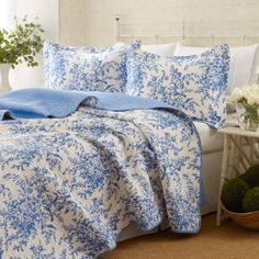 The Laura Ashley Bedford quilt set is a blue and white floral desig...