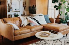 I love those pillows. Love that fur blanket. Leather couch is a MUST. This one is a three seater but with the extension we love. We'd have this couch and the single chair I pinned earlier.  Darker leather though.