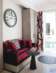 A guest room features a daybed dressed with striped Ralph Lauren Home fabrics; the clock is by Restoration Hardware.