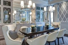 Gray dining room features a pair of ring chandeliers, Cece 5-Light Chandeliers, illuminating an espresso dining table lined with ivory leather dining chairs as well as  ivory leather wingback dining chairs placed at each end of the table atop a gray Moroccan trellis rug.