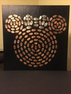 "Disneyland squished pressed Pennies board on a 24"" x 24"" canvas painted black. Display"
