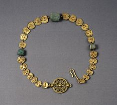 "3rd AD Roman gold necklace with three agate beads, open-work disk at hook-and-eye closure, 25 heart-shaped plaques.  Held at Walters (Acc 57.524).  In photo: 14 3/16"" h x 3 9/16"" w x 1/4"" d x 7 1/16"" l (36 x 9 x 0.71 x 17.9 cm); at clasp: 15/16"" w (2.34 cm).  From end-to-end: eye; open-work disk; 7 plaques; agate bead; 6 plaques; agate bead; 6 plaques; agate bead; 6 plaques; hook closure."