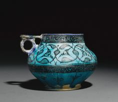 A Kashan cup with stylised vegetal decoration and inscriptions under a transparent turquoise glaze, Persian, early 13th century