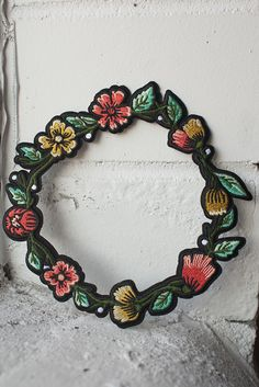 "Embroidered floral wreath with iron-on backing can be used to frame and complement your other favourite patches - perfect on the back of a jacket! Coming in at just under 6.5"" circumference, the wreath can fit a 3.5"" circular patch inside it. Follow the instructions below to affix this patch to a garment of your choosing (click to enlarge)! For items that will be washed, sewing on is recommended."