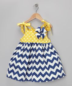 Decorated with darling chevrons and polka dots, this dreamy duo fashions a sublime sunny day look for any little sweetie. The classically-colored dress features charming tie-straps, while the complementary bow acts as a fetching accent up top.Includes dress and clip100% cottonMachine wash; hang dry