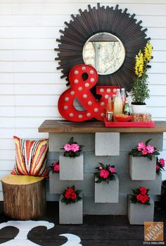 This cinder block planter serves double duty as a bar and drink station! Warm it up it with personal touches and a sunburst mirror!