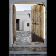 Entrance to house on Greek Island: I wish for an entrance like this, I like it when its quite simple! Of course I would love to paint the wooden gate in a fun color like red, blue or yellow. Style Ibiza, Spanish Courtyard, Myconos, Flagstone Flooring, My House, Future House, Wooden Gates, Entry Gates, Old Doors