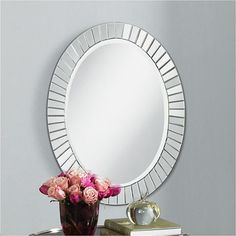 An arrangement of mini mirrors creates a sparkling border for this oval wall mirror design.